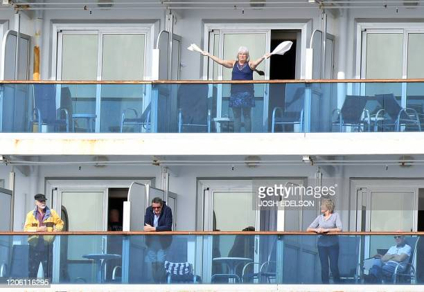 TOPSHOT A woman gestures as other people look on from aboard the Grand Princess cruise ship operated by Princess Cruises as it maintains a holding...