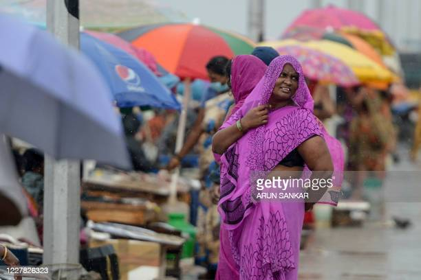 A woman gestures as she covers her head with her saree near fish vendors at a market during rain in Chennai on July 29 2020
