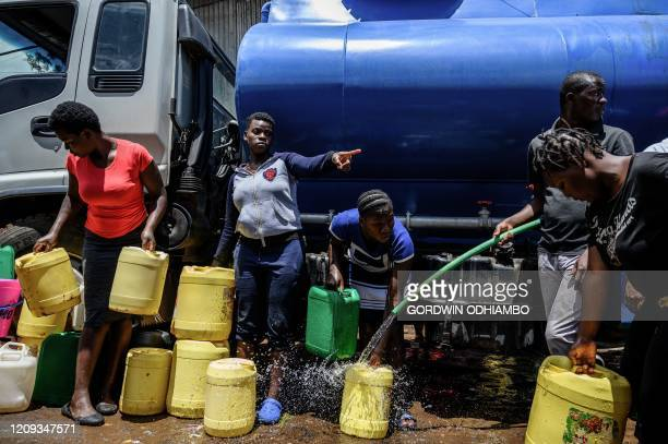 A woman gestures as she queue with other residents who brought their jerrycans to fill them with free water distributed by the Kenyan government at...