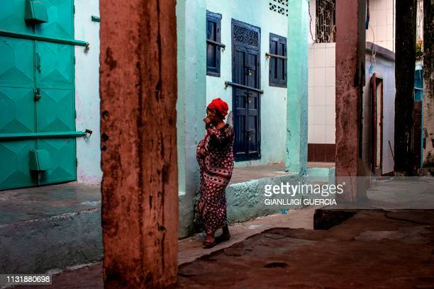 A woman gestures as she walks past a closed shop at dusk on March 21 in the medina of Mutsamudu the capital of Anjouan Island Comoros People of...