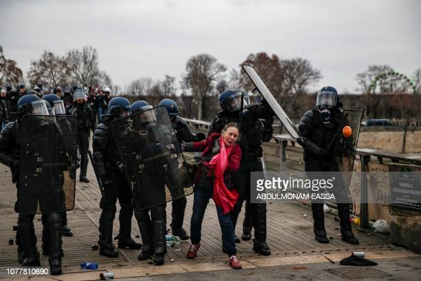 A woman gestures next to riot police officers trying to protect themselves from projectiles on January 5 2019 in Paris during an antigovernment...