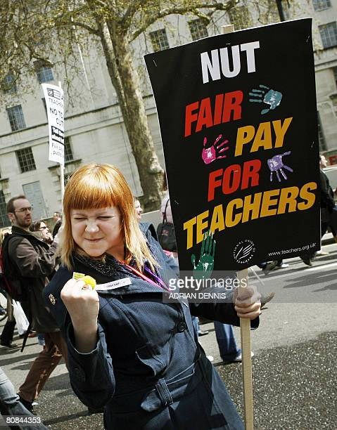 A woman gestures towards Downing Street as she marches along Whitehall during the teachers and general workers protest in central London on April 24...