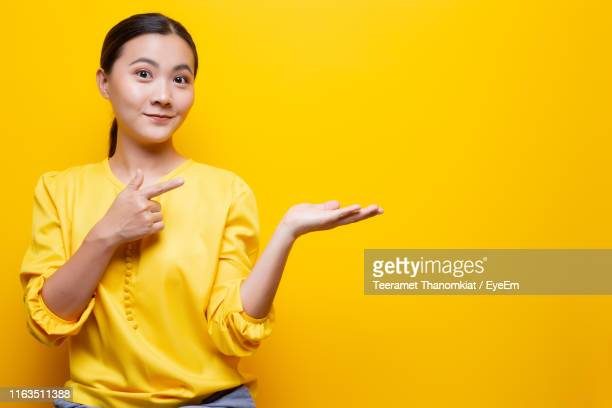woman gesturing against yellow background - yellow background stock pictures, royalty-free photos & images