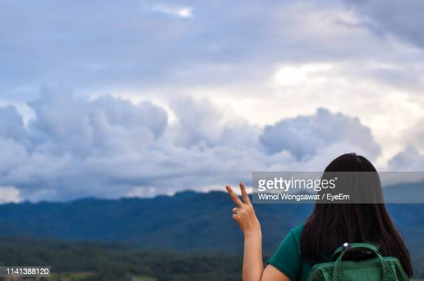 woman gesturing peace sign against cloudy sky - wimol wongsawat stock photos and pictures