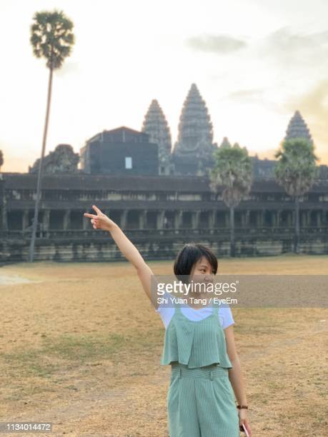 woman gesturing peace sign while standing against temple - traditionally cambodian stock pictures, royalty-free photos & images