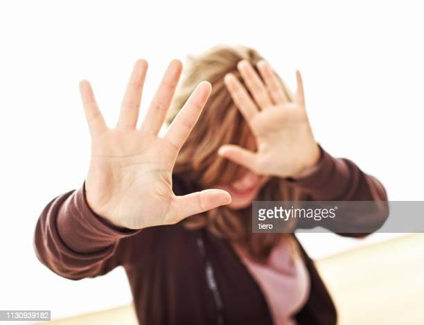 woman gesturing stop sign against white background - violences conjugales photos et images de collection