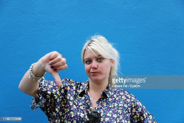 woman gesturing thumbs down against blue wall - disappointment stock pictures, royalty-free photos & images