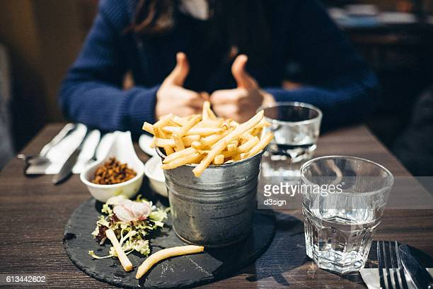 Woman gesturing thumbs up while having a bucket of french fries in a restaurant