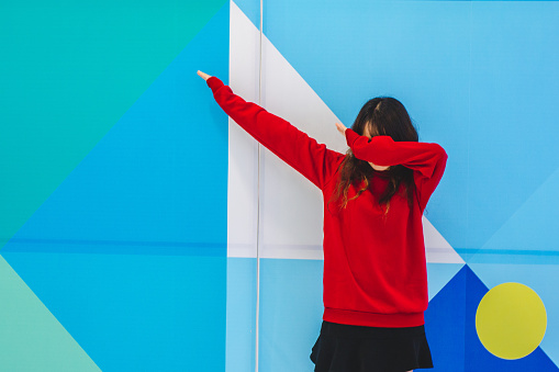 Woman Gesturing While Standing Against Blue Wall - gettyimageskorea