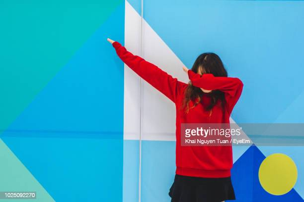 woman gesturing while standing against blue wall - bontgekleurd stockfoto's en -beelden