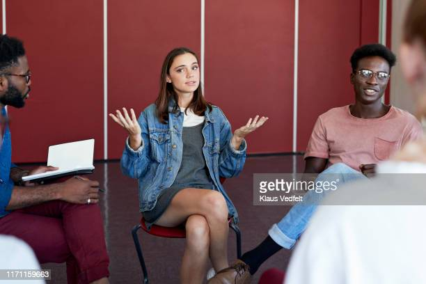 woman gesturing while talking in group therapy - information overload stock pictures, royalty-free photos & images
