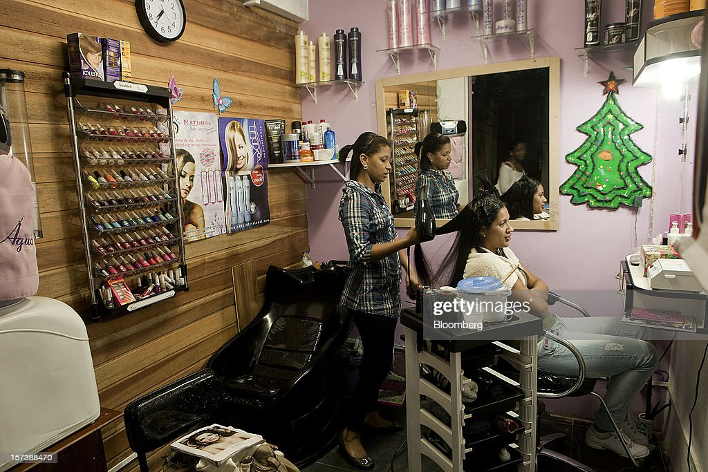 A woman gets a haircut at a salon in the Rocinha slum of Rio de Janeiro, Brazil, on Wednesday, Nov. 28, 2012. About 56 percent of the 12 million people who live in slums like Rocinha were considered middle class in 2011, up from 29 percent in 2001, according to a study this year by Instituto Data Popular, a Sao Paulo-based research group. Photographer: Dado Galdieri/Bloomberg via Getty Images