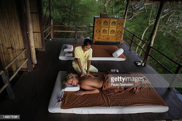 A woman gets a Thai massage in the open air massage sala at the Kamalaya Wellness Sanctuary June 18 2012 Thailand's official tourism body the Tourism...