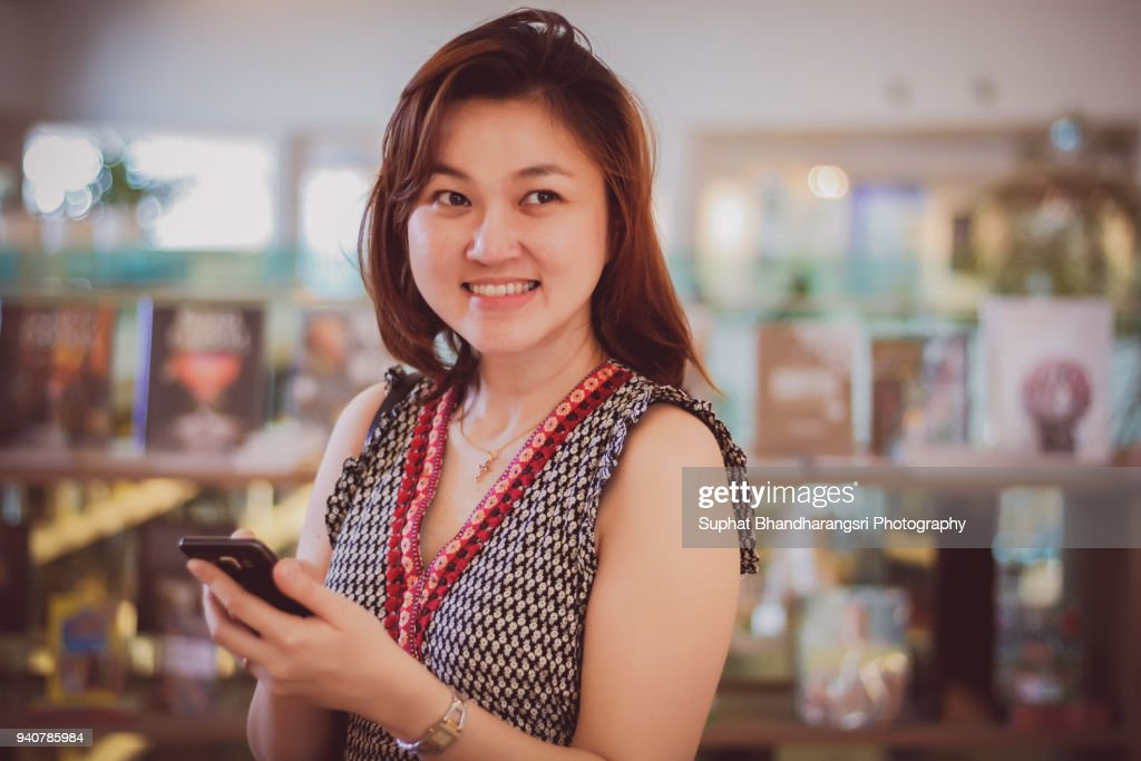 Woman gets app notification in bookstore : Stock Photo