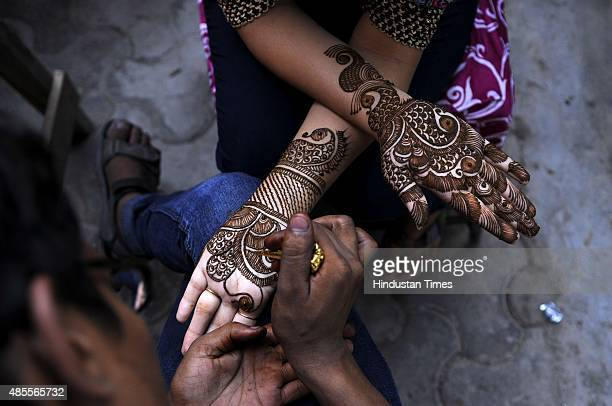 A woman gets her hands decorated with Henna along the roadside on the eve of Raksha Bandhan on August 28 2015 in Noida India Celebrating the bond...
