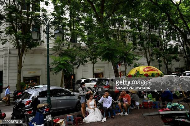 Woman gets her make up done during the couple's wedding photo session along a street in Hanoi on June 17, 2020.