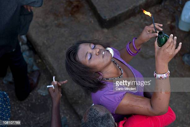 A woman gets possesed by Gede next to a cross dedicated to Baron Samedi the head of the Gede family of spirits the spirits of the dead in the...