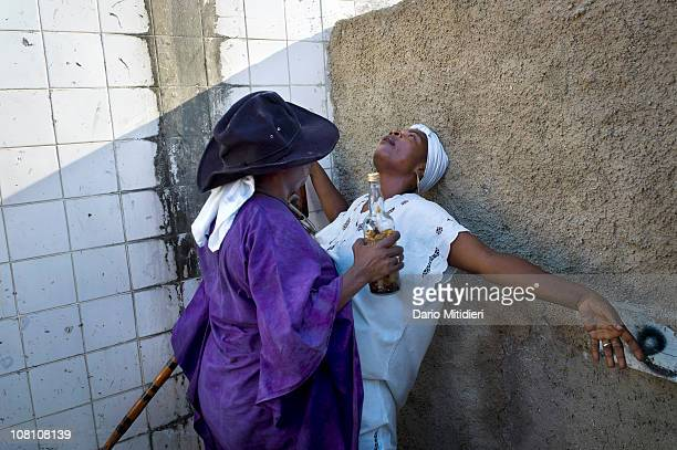 A woman gets possesed by Gede next to a cross dedicated to Baron Samedi in the National Cemetery of PortauPrince Haiti on All Saints' Day Nov 1 where...