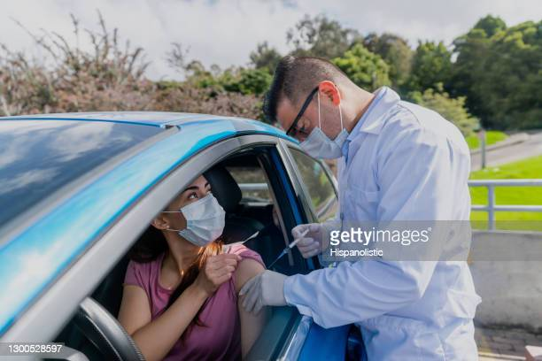 woman getting a covid-19 vaccine at the drive through - drive through stock pictures, royalty-free photos & images