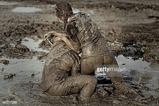 woman getting a fight lesson in mud