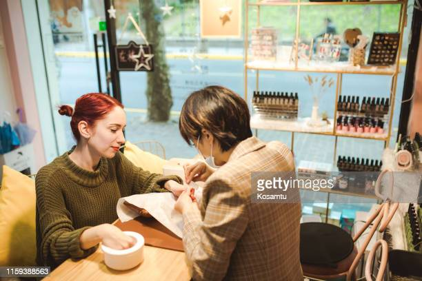 woman getting a manicure - nail salon stock pictures, royalty-free photos & images