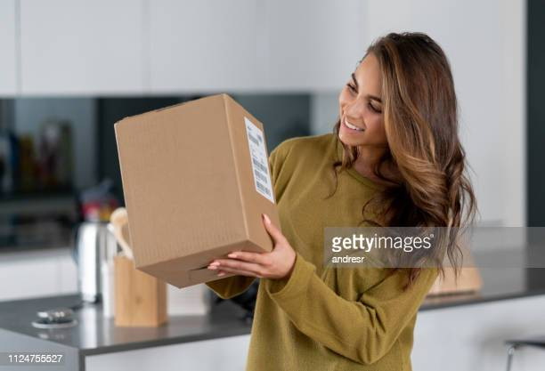 woman getting a parcel in the mail at home - package stock pictures, royalty-free photos & images