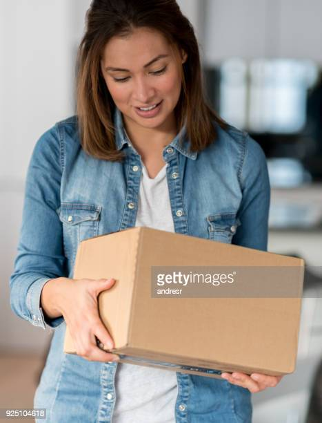 Woman getting a parcel in the mail at home
