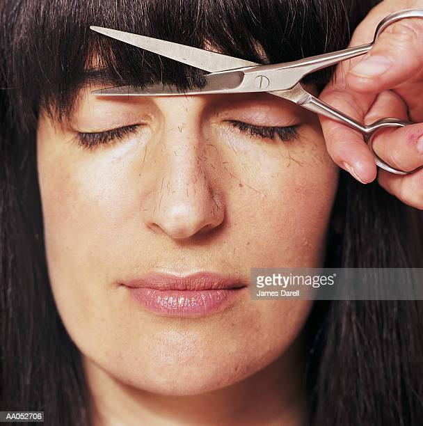 Woman getting bangs cut, eyes closed, close-up