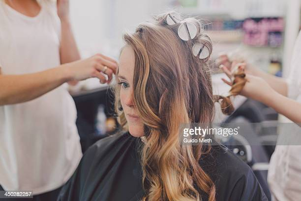 woman getting curls from hairdressers - hairdresser stock pictures, royalty-free photos & images