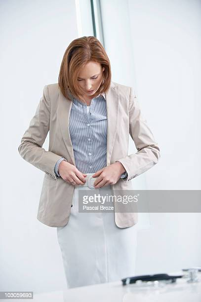 Woman getting dressed in an office