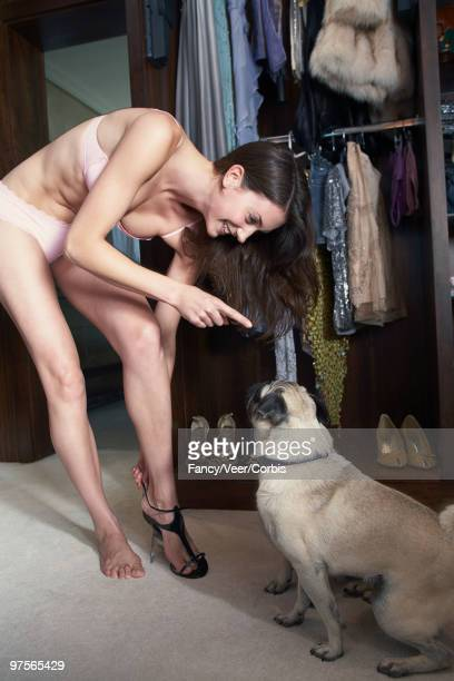 Woman getting dressed talking to her dog
