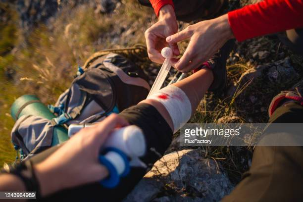 woman getting first aid treatment after a hiking injury - first aid kit stock pictures, royalty-free photos & images