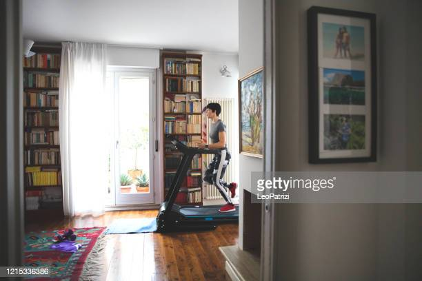 woman getting fit and doing home training in the living room - treadmill stock pictures, royalty-free photos & images