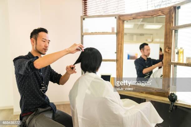 彼女の髪を得る女性カットし、スタイルのヘアサロンで