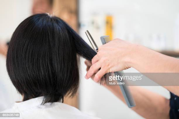 woman getting her hair cut and styled at a hair salon - tdub_video stock pictures, royalty-free photos & images