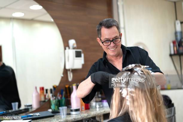 woman getting her hair dyed at salon - highlights hair stock pictures, royalty-free photos & images