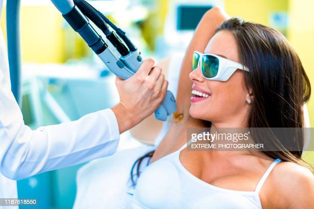 a woman getting her hair removed from armpit are by a laser treatment in a beauty salon - armpit hair woman stock pictures, royalty-free photos & images