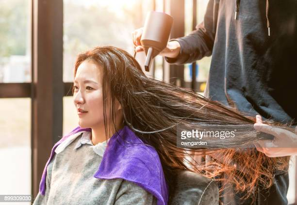 Woman getting her hair styled at hairdressers