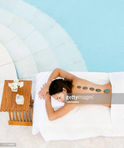 Femme se massage aux pierres chaudes dans un centre de villégiature de luxe avec spa