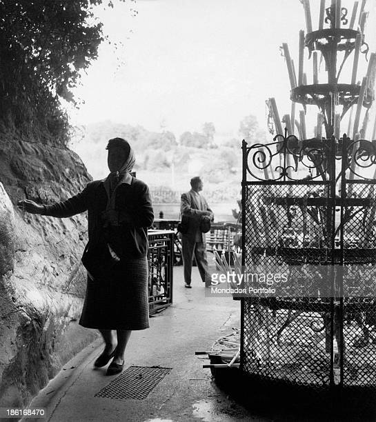 A woman getting in the Grotto of Massabielle during the centenary of the apparitions of Our Lady to Saint Bernadette Soubirous Lourdes 22nd November...