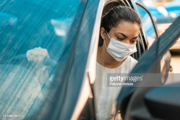 woman getting into her car with a protection mask - entering stock pictures, royalty-free photos & images