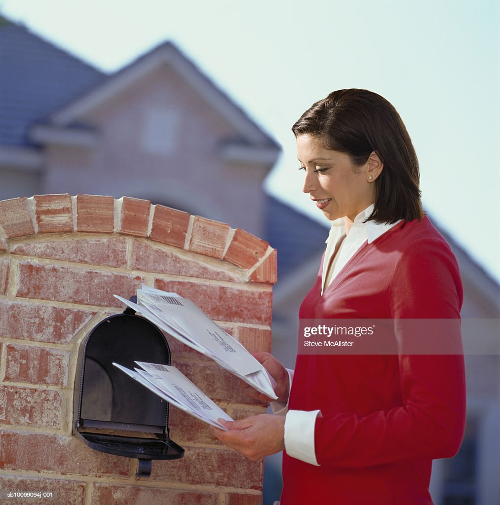 Woman getting mail from mailbox : Stockfoto