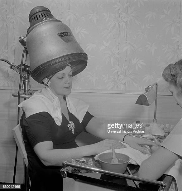 Woman Getting Manicure while Drying Hair at Hair Salon Eighth Street New York City New York USA Marjorie Collins for Office of War Information...