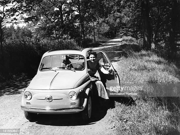 Woman getting out from a car Fiat 500 stationary in a country road Italy June 1957