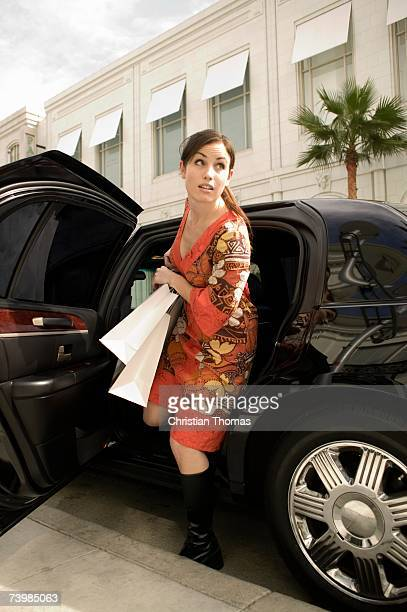 a woman getting out of a car with shopping bags, los angeles, california, usa - 降り立つ ストックフォトと画像
