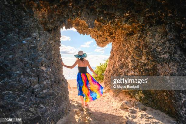 woman getting out of a cave overlooking the sea, yucatan peninsula, mexico - grotto stock pictures, royalty-free photos & images