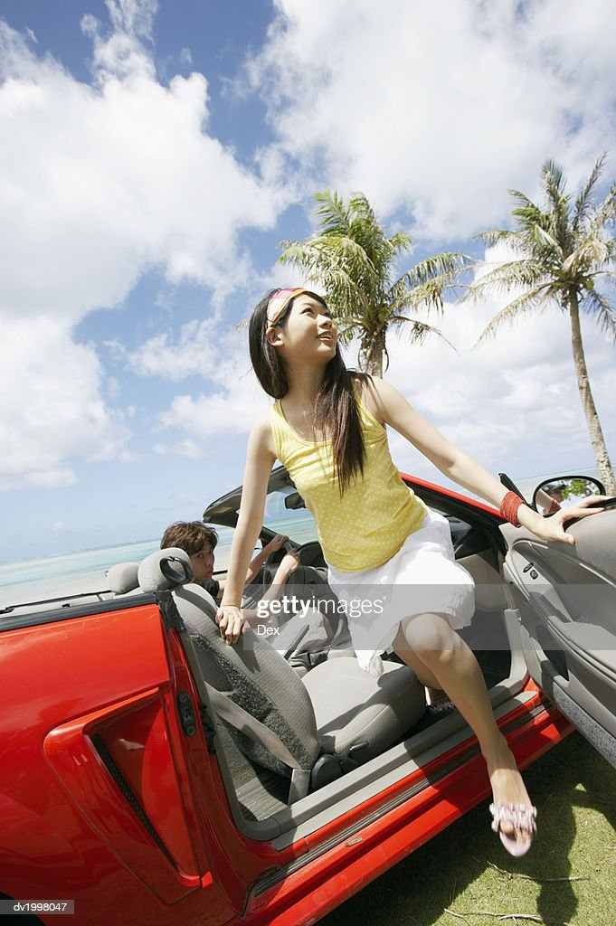 Woman Getting Out of a Convertible by the Beach : Stock Photo
