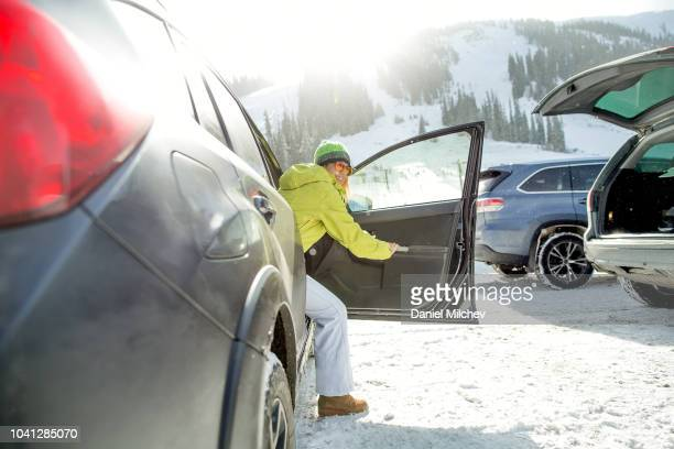 woman getting out of a vehicle at a ski resort parking lot while snowing. - 降り立つ ストックフォトと画像