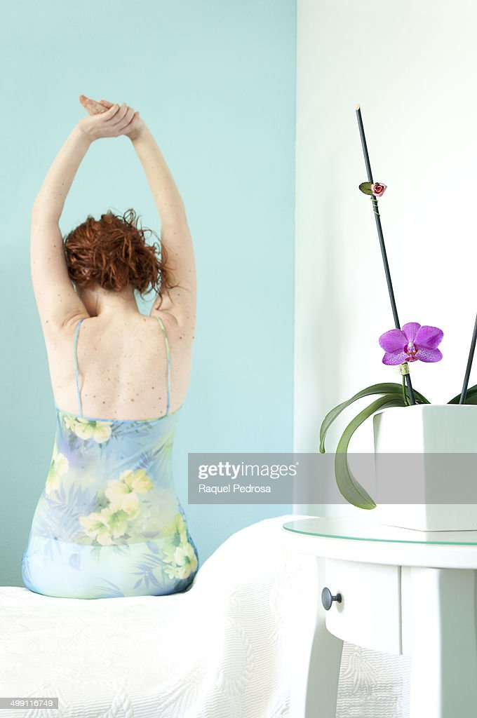 Woman getting out of bed in the morning : Stock Photo