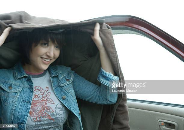 woman getting out of car, holding up jacket over head - coat stock pictures, royalty-free photos & images